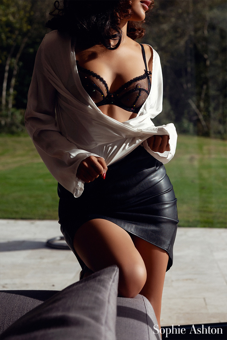 Looking sensual in a leather skirt, posing in her Home Counties home